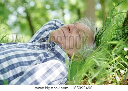 Senior man taking a nap laying down in grass
