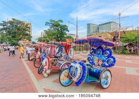 MALACCA, MALAYSIA - AUGUST 12, 2016: The decorated trishaw parking in a Famosa Castle in Malaccatourists and local people can seen around the Famosa Castle in Malacca