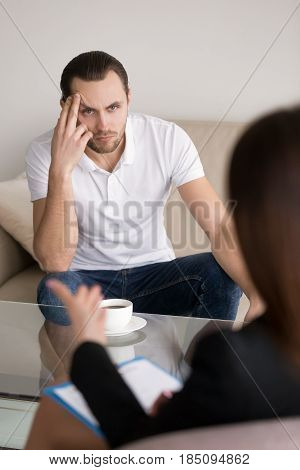 Serious concerned male patient sitting on the couch listening attentively to advices of psychotherapist, businessman negotiating with female partner, meeting with lawyer or financial advisor
