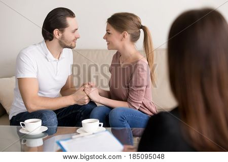 Excited loving couple sitting on sofa holding hands looking in the eyes, meeting with wedding planner, choosing place for honeymoon trip, successful marriage therapy with family psychologist