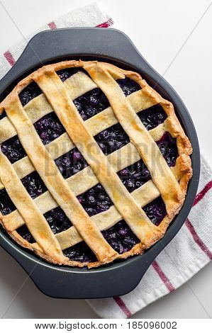 Homemade blueberry pie cooling off in a baking pan viewed from above. It's a popular American and Canadian dessert, simple yet so delicious. It is typically eaten in the summer (when blueberries are in season).