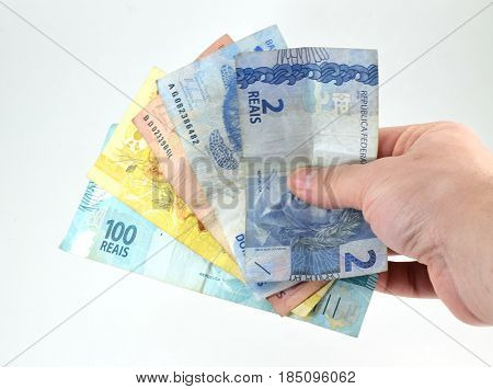 Hand holding Brazilian currency bills (real and reais) isolated white background