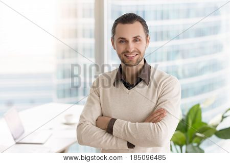 Smiling happy young businessman standing in office with arms crossed. Business owner, prospective promising manager, successful career in big corporation, company director looking at camera headshot