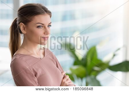 Head shot portrait of pensive young woman at home office interior with arms crossed, looking at the window, dreaming of future, thinking about something, lost in thoughts and ideas, copy space