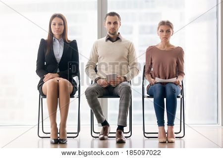 Group of ambitious confident businesspeople sitting on chairs in a row looking at camera, candidates waiting their turn for job interview, feeling focused and nervous. Job search concept. Full length