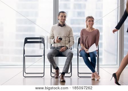 Confident businesswoman walking by male and female job candidates sitting on chairs, following her with their eyes, fake artificial smile, pretending amiability, mask of pretense, social artifice