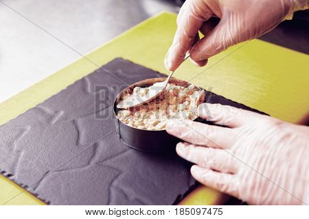 Chef is serving appetizer on slate plate with metal ring, commercial kitchen, toned image