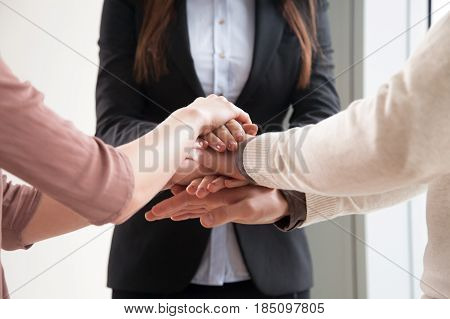 Close up of three people joining hands together, starting joint business, common goal, successful team building, motivated enthusiastic co-workers starting work on project, running company together