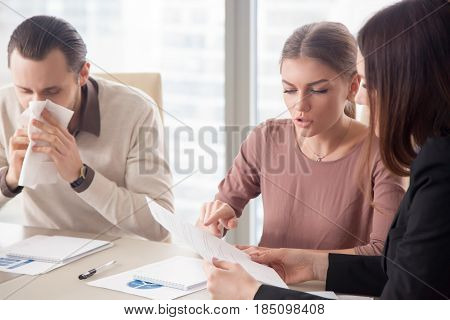 Young businessman with handkerchief caught flu sitting among colleagues on meeting discussing work issues. Risk to take infection, boost immune system, seasonal allergy, business healthcare concept