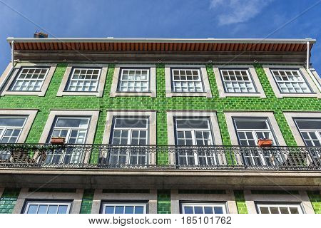 Green tiled residential building on Flores Street in Porto Portugal