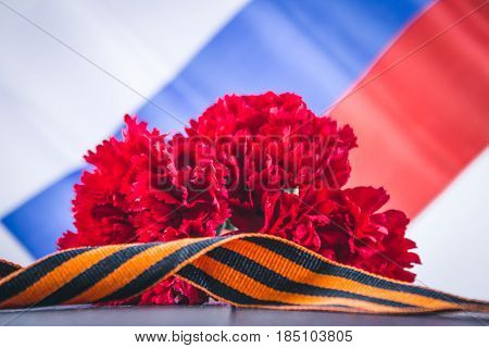 Carnation And Ribbon Of St. George, As A Symbol Of Victory Against The Background Of The Russian Fla