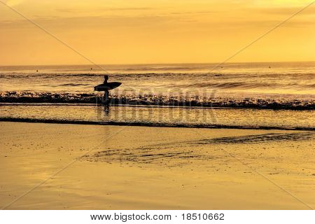 A surfer going in the ocean at sunrise