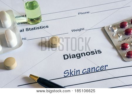 Diagnosis skin cancer written in the diagnostic form and pills
