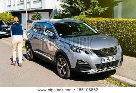 STRASBOURG FRANCE - APR 8 2017: Elegant French woman walking near beautiful Peugeot 3008 crossover SUV. The Peugeot 3008 is a compact crossover unveiled by French automaker Peugeot in May 2008