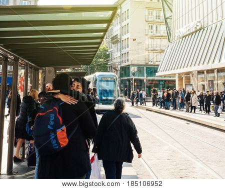 STRASBOURG FRANCE - APR 27 2017: Couple hugging as tramway arriving in station - rush hour - Busy center of the French city of Strasbourg Alsace with tramways and commuters pedestrians walking under architectural station l'Homme de Fer on a sunny evening
