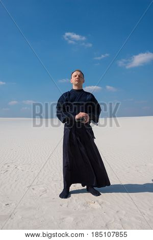 Concentrated Man In Traditional Japanese Clothes Stands And Meditates