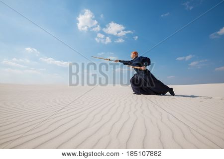 Man In Traditional Japanese Clothes Makes A Deep Lunge With A Shinai