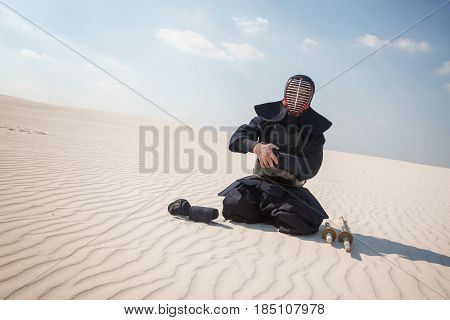 Warrior, Man In Traditional Armor, Bogu For Kendo Sits  In A Desert