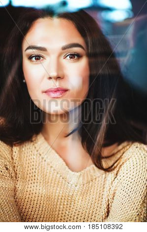 Close up portrait of 35-40 year old woman with black hair through the window