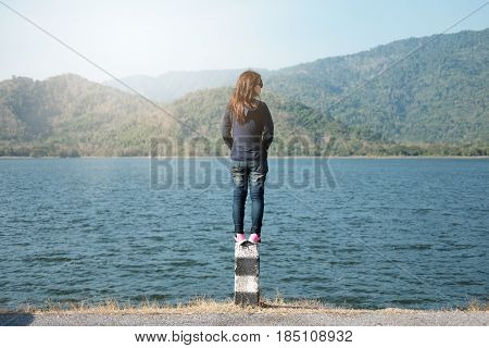 Woman Standing On Pillar Roadside Front Of Her Have Big Lake And Mountain Background. This Image For