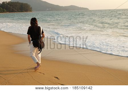 Young Girl Walking On Beach In Evening Time And Small Wave Impact To Sand Beach. This Image For Land