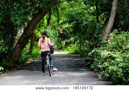 Young Girl After Riding Bicycle She Stopped On Road In Public Garden And Looking Forward, This Image