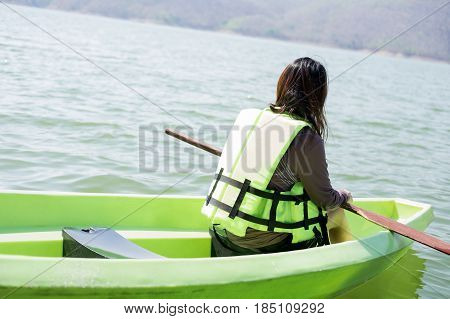 Young Woman Equip Life Jacket Sitting Relaxing On Prow Have Peddle On Lap Herself. She Looking Side