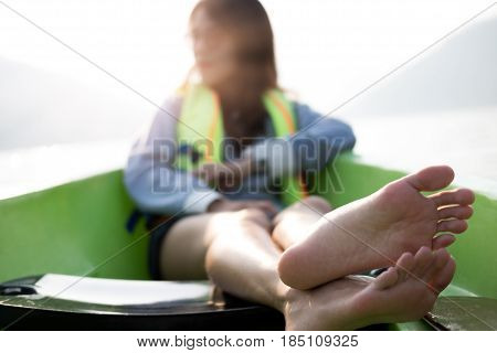 front view focus foot of young woman equip life jacket sitting relaxing on prow. she looking side around herself have sea and sunset background. this image for travelnature and portrait