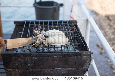 Hand Of Someone Are Grill Fresh Squid On Hot Stove With Knife. This Image For Food And Aquatic Anima