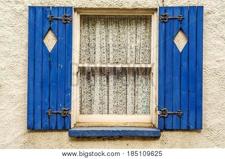 Window with wooden shutters diamond shape cut in shutters shutters painted in blue beautiful patterned curtains architecture
