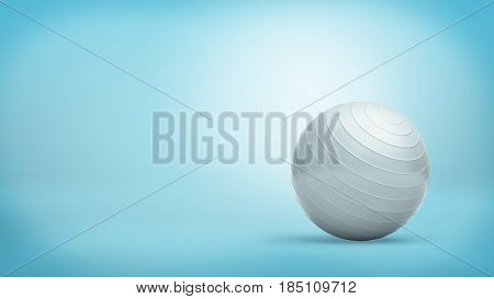 A silver ridged balance ball made of shining rubber placed on blue background. Fitness equipment. Sport and exercising. Yoga and stretching.