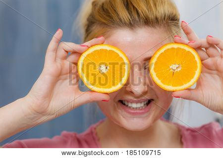 Woman Having Gel Mask On Face Holding Orange