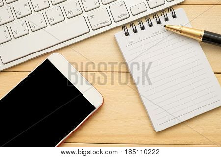 Top View. Keyboard, Pen, Notebook Paper And Mobile Phone All Of This Putting On Wooden Background. T