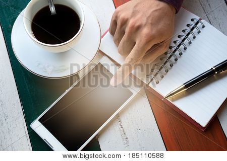 Top View. Hand Of Business Man Touching On Screen Mobile Phone And Have Coffee Cup With Coffee, Pen