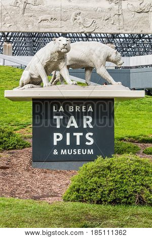 LOS ANGELES, CALIFORNIA - FEBRUARY 19, 2017:  Saber tooth tiger sculpture on entrance sign at the La Brea Tar Pits, in Hancock Park, an urban Ice Age fossil excavation site/museum.