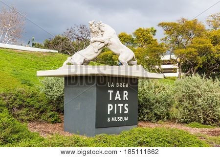 LOS ANGELES, CALIFORNIA - FEBRUARY 19, 2017:  Statue of fighting saber tooth tigers on entrance sign at the La Brea Tar Pits, an urban Ice Age fossil excavation site/museum.