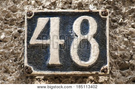 Old retro weathered cast iron plate with number 48 closeup