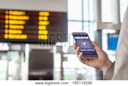 Online check in with mobile phone in airport. Woman checking in to flight with smartphone on the web. Internet self service provided by airline. Hand holding cellphone. Timetable in the background.