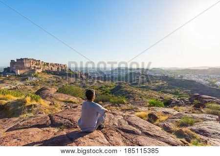 Tourist Sitting On Rock And Looking At Expansive View Of Jodhpur Fort From Above, Perched On Top Dom