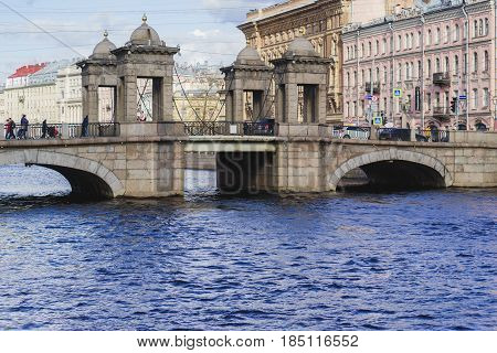 RUSSIA St.Petersburg - APRIL 8 2017 Lomonosov bridge reflected in the water of the river of Fontanka St. Petersburg on the bridge are people sunshine day
