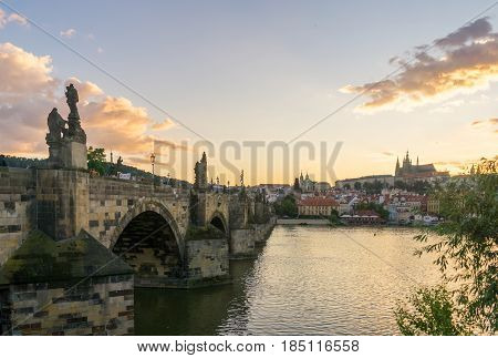 Looking across the side of the Charles Bridge in Prague at sunset with Prague Castle visible on the other side of the Vltava River.