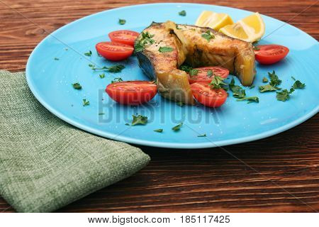 Steak of sturgeon with lemon and tomatoes. Healthy nutrition concept.