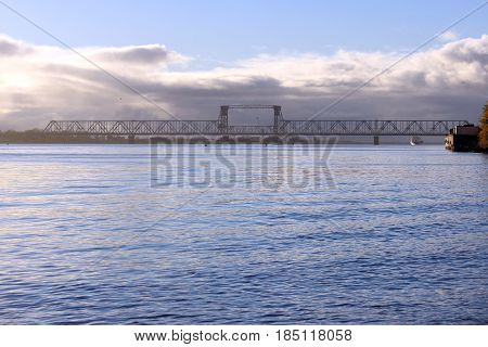 white cumulus clouds pass bridge over the Northern Dvina River.