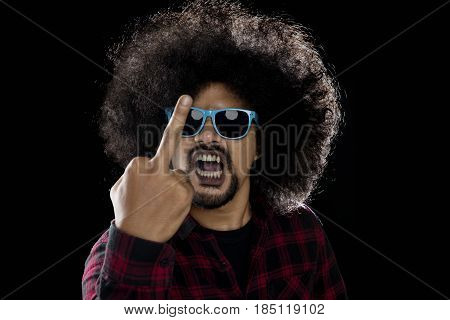 Afro man wearing sun glasses showing middle finger as his angry expression with dark background