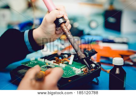 Airplane on the radio control. Repair, soldering iron in the hands of the guy.