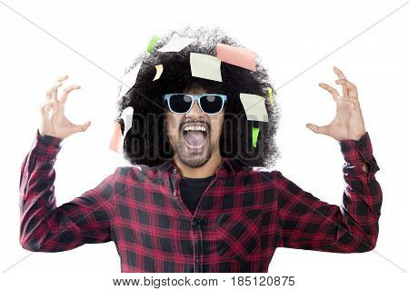 Anxious man wearing sun glasses screaming with blank sticky notes over his head isolated on white background