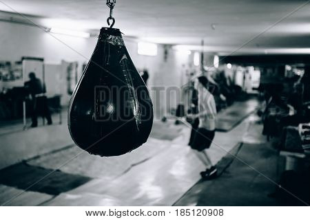 Punching bag in the gym. Against the backdrop of athletes. Gym is a cellar. Russia.
