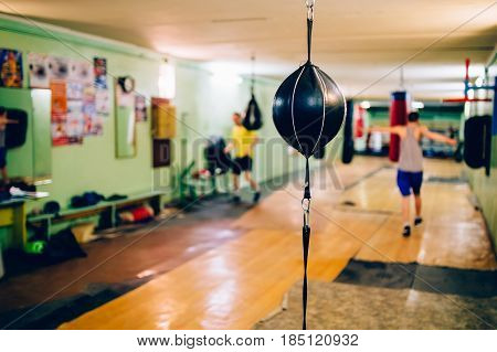 Punching bag in the shape of a ball in the gym. Against the backdrop of athletes.