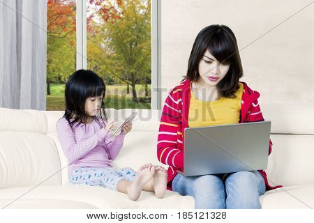 Young Asian woman looks busy working with a laptop computer while her daughter playing a mobile phone on the sofa at home