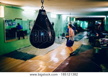 A boxer guy is wearing a Punching bag in the gym. Against the backdrop of athletes. Gym is a cellar. Russia.